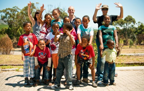 A group of smiling children and their teachers outside a Graff Leadership Centre